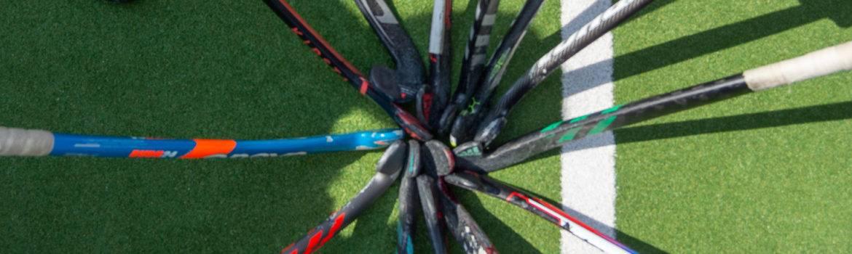 Hockeysticks in een ster bij elkaar.